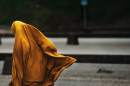 Woman's Trust London domestic violence free counselling charity - image of a woman in a mustard coloured hijab with her back to the camera - Read real life stories from survivors of domestic abuse